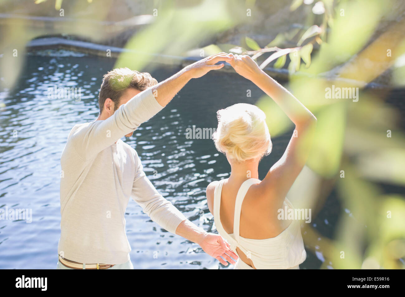 Couple dancing by pool - Stock Image