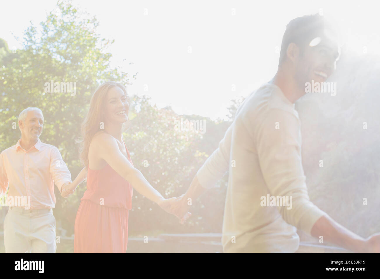 Sunbeam over friends holding hands outdoors - Stock Image