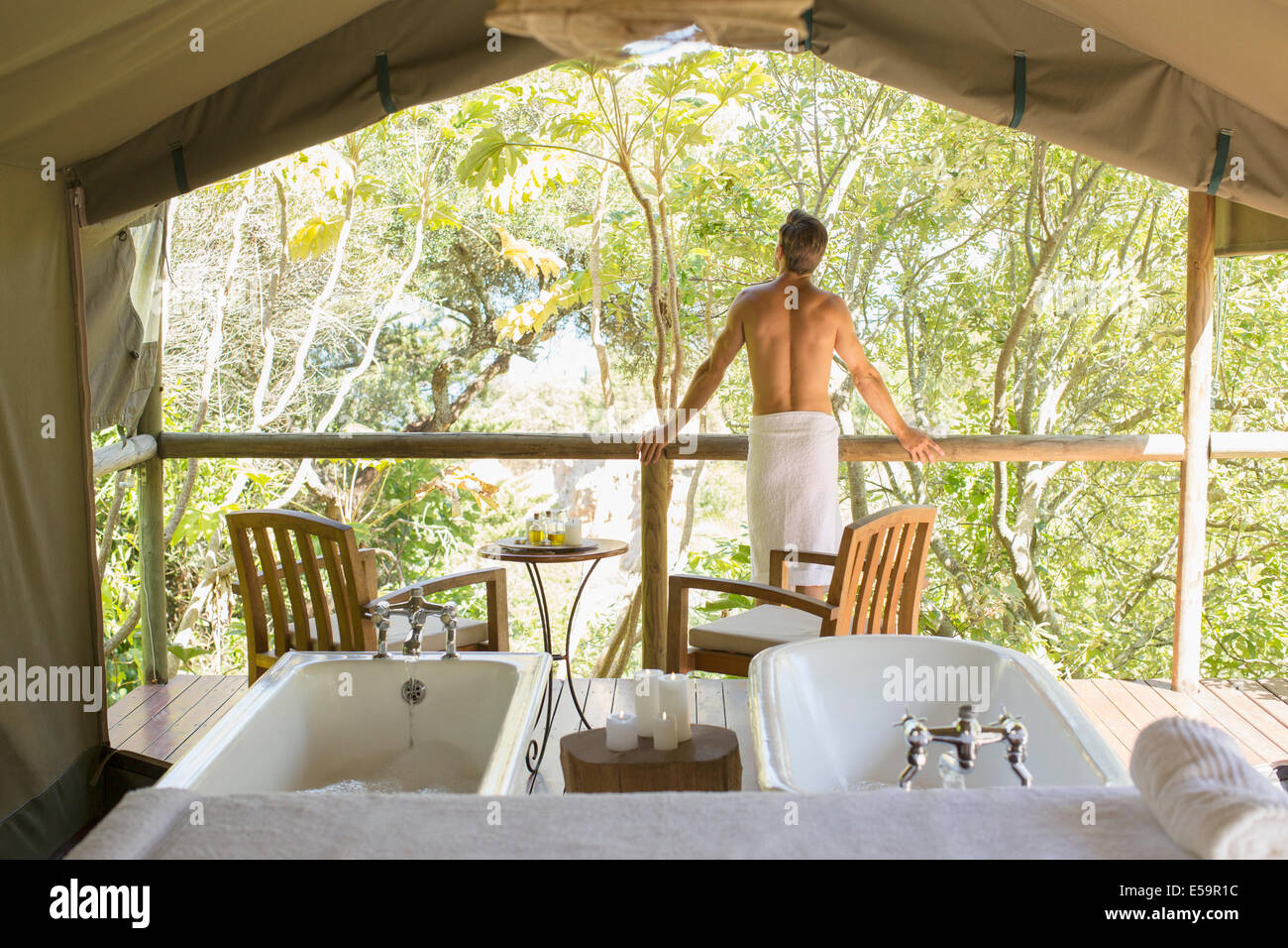 Man standing in ornate outdoor spa - Stock Image