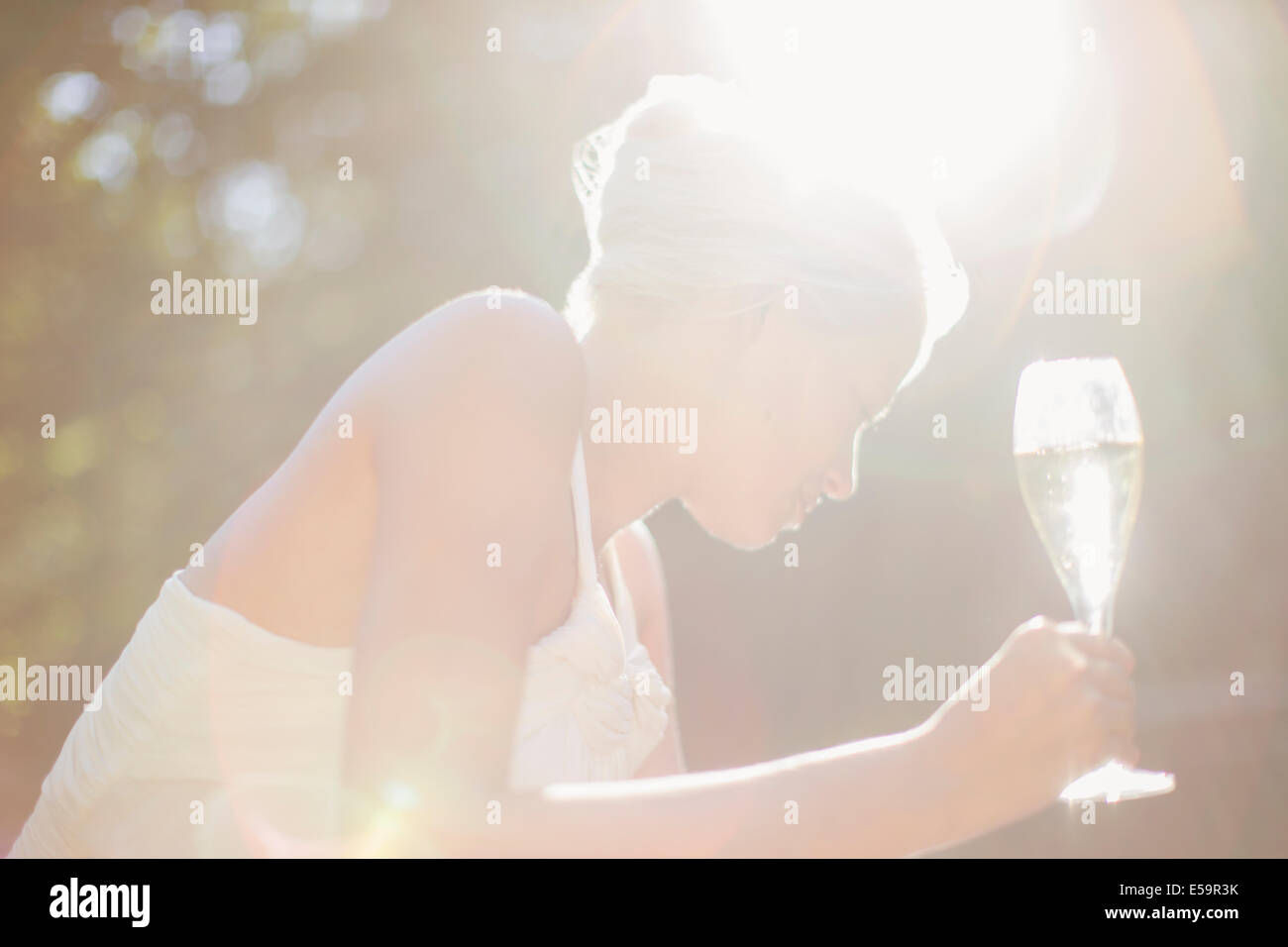 Woman drinking champagne outdoors - Stock Image