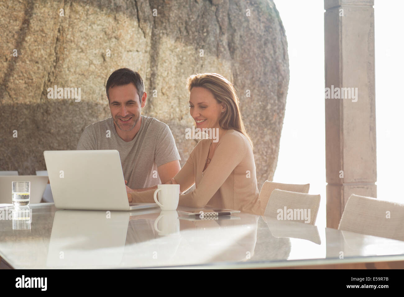 Couple using laptop at breakfast - Stock Image
