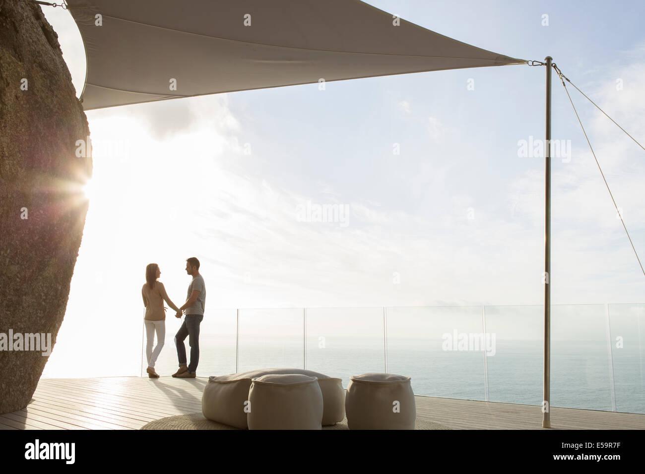Couple standing on modern balcony - Stock Image