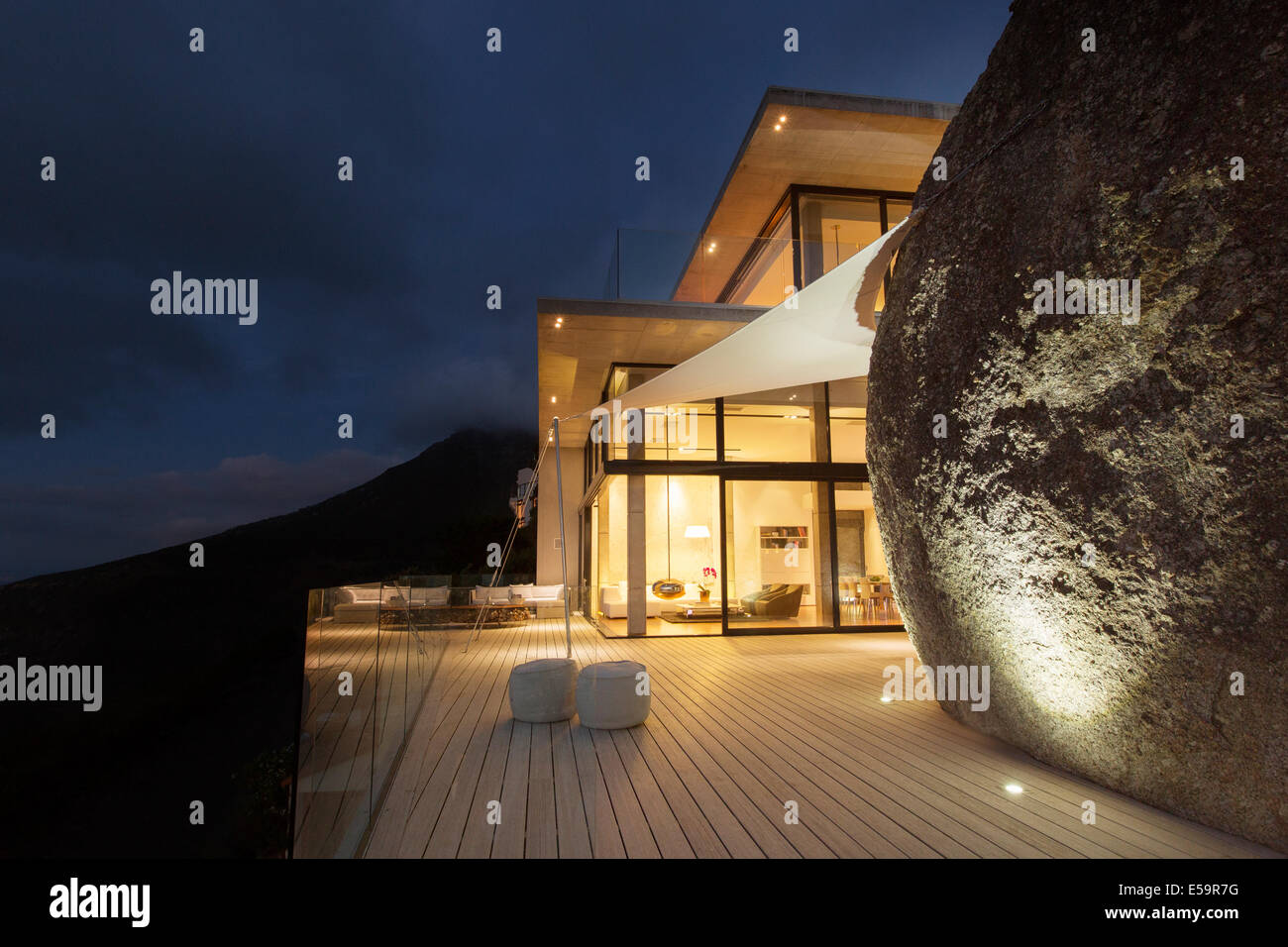 Illuminated modern house with rock feature and balcony - Stock Image