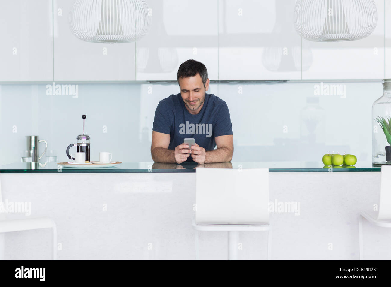 Man using cell phone in modern kitchen - Stock Image