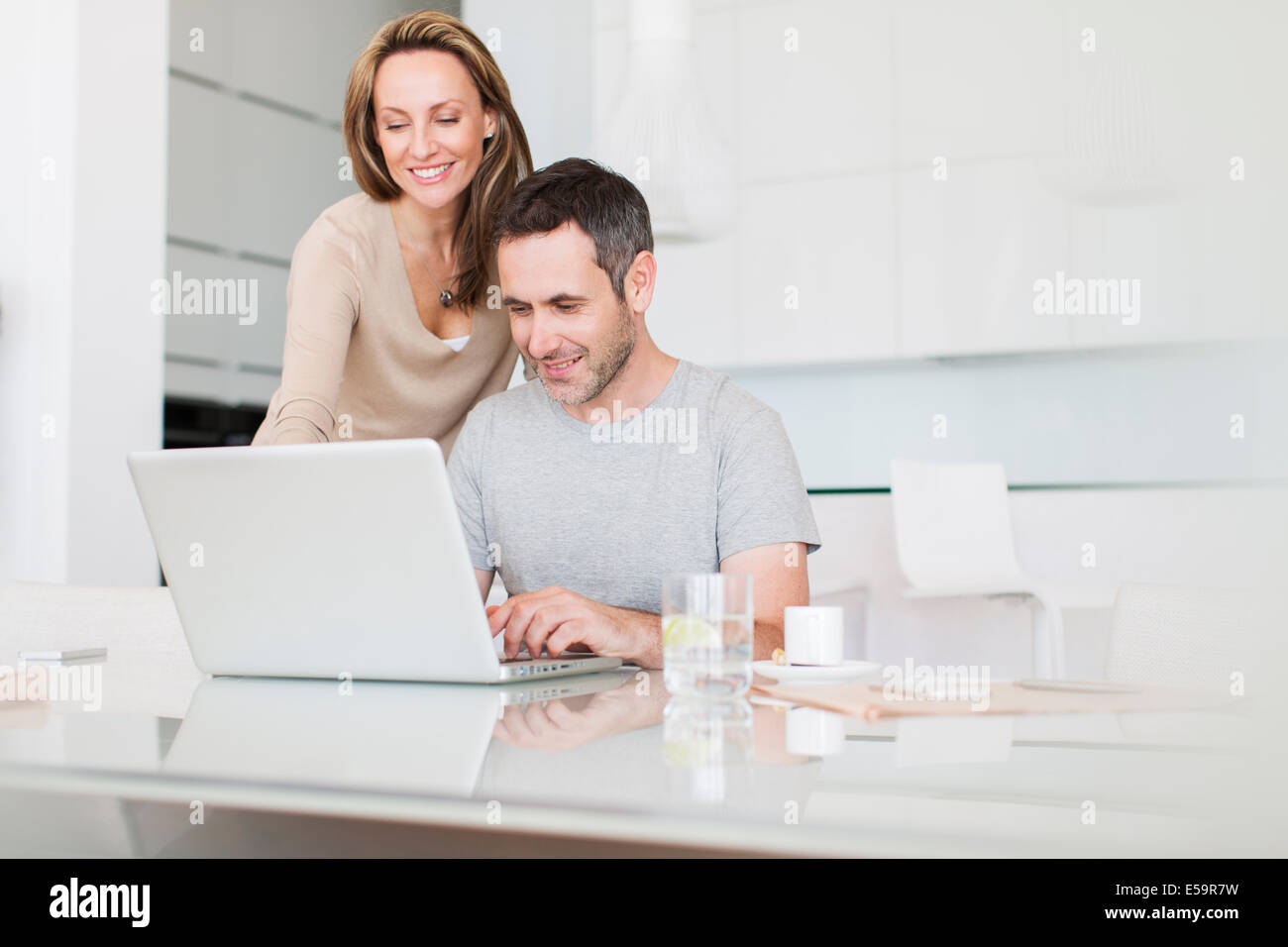 Couple using laptop at breakfast table - Stock Image