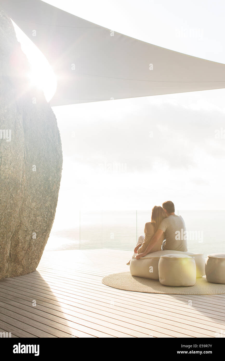 Couple relaxing together on modern balcony - Stock Image