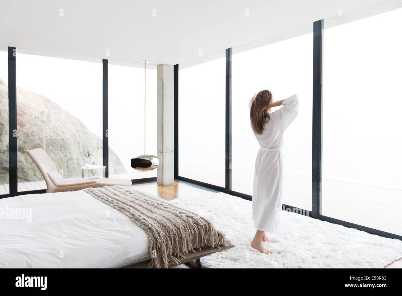 Woman wearing bathrobe in modern bedroom - Stock Image