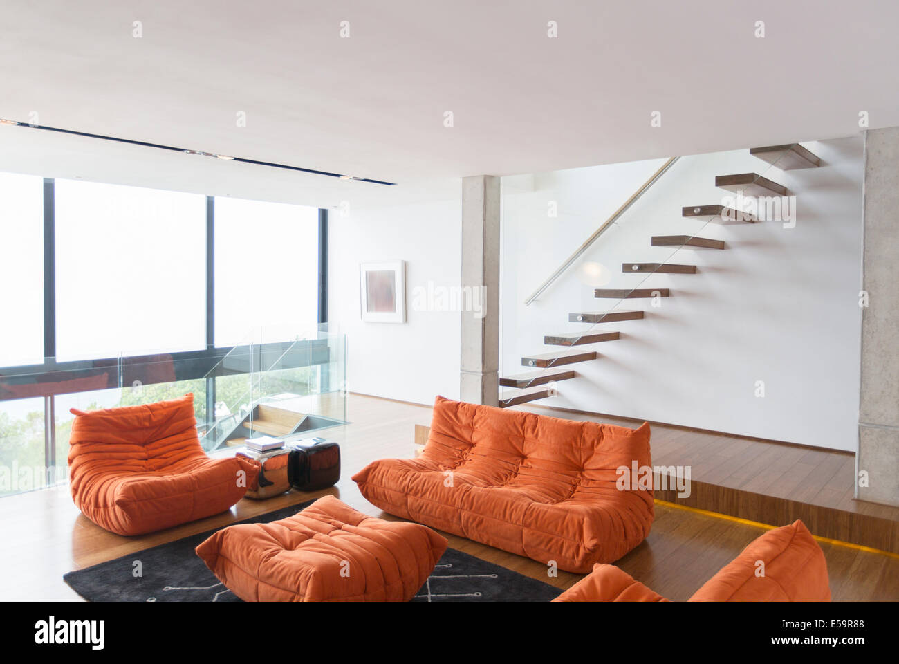 Sofas and staircase in modern living room - Stock Image