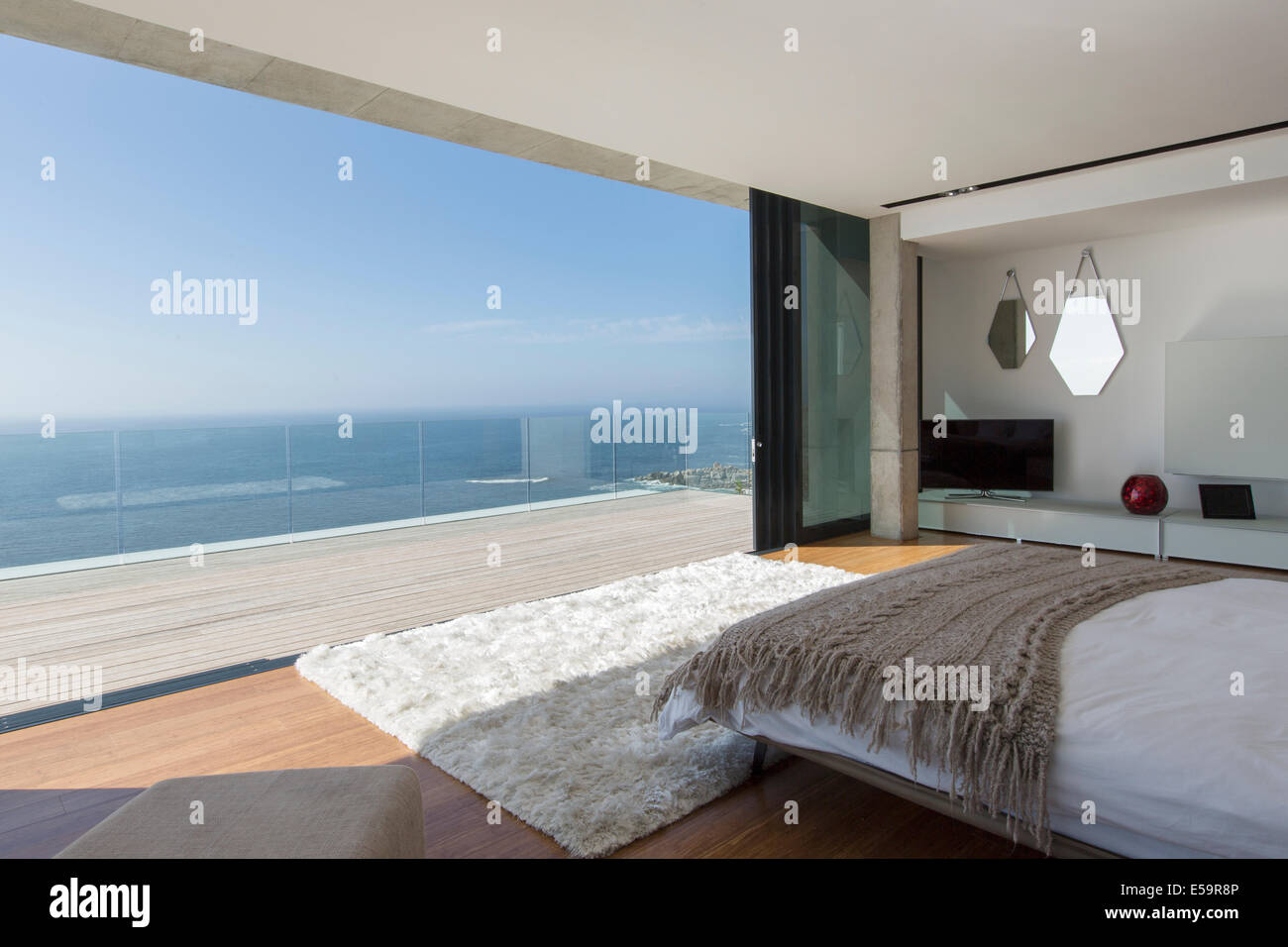 Modern bedroom overlooking ocean - Stock Image