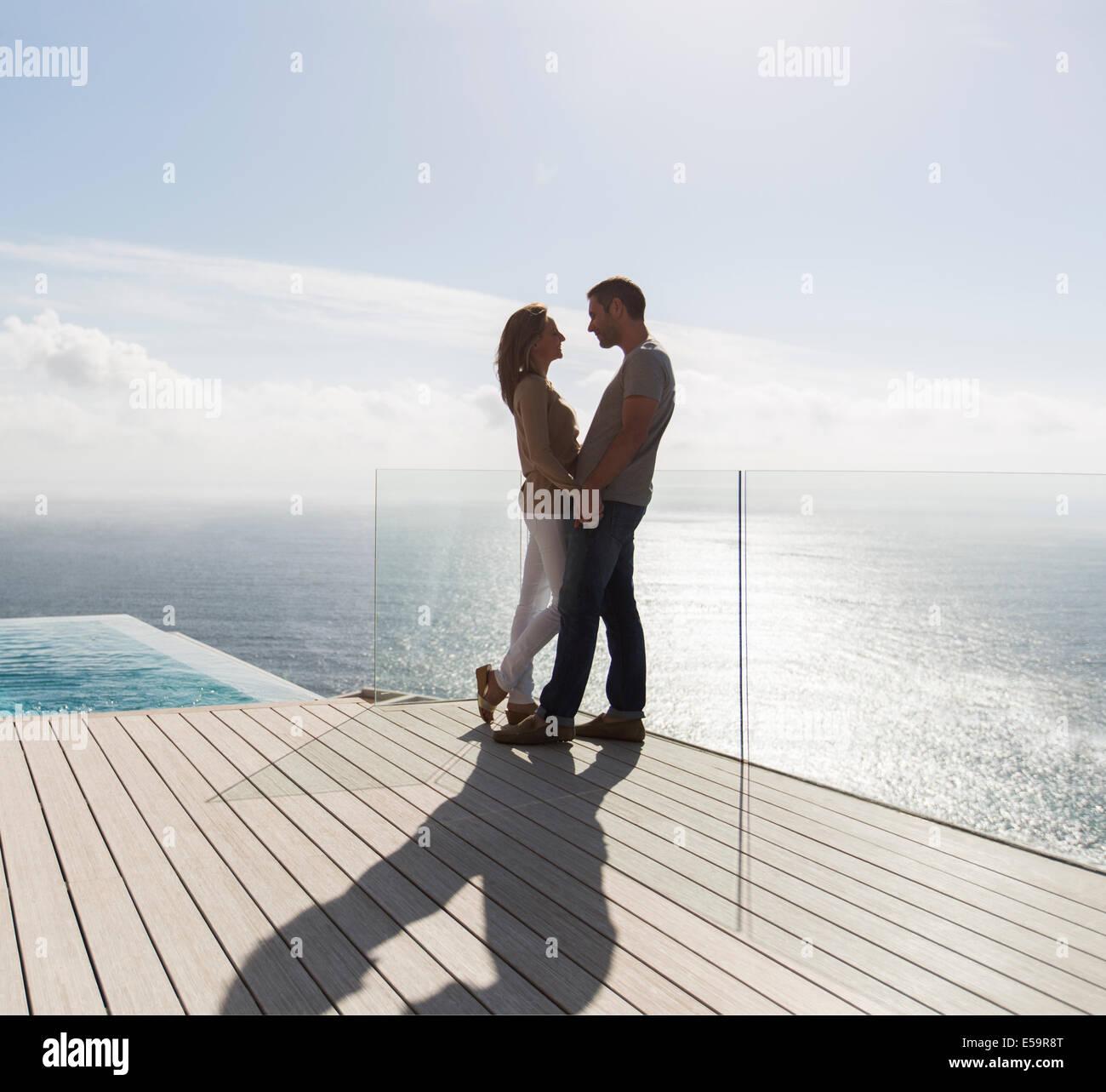Couple on modern balcony overlooking ocean - Stock Image