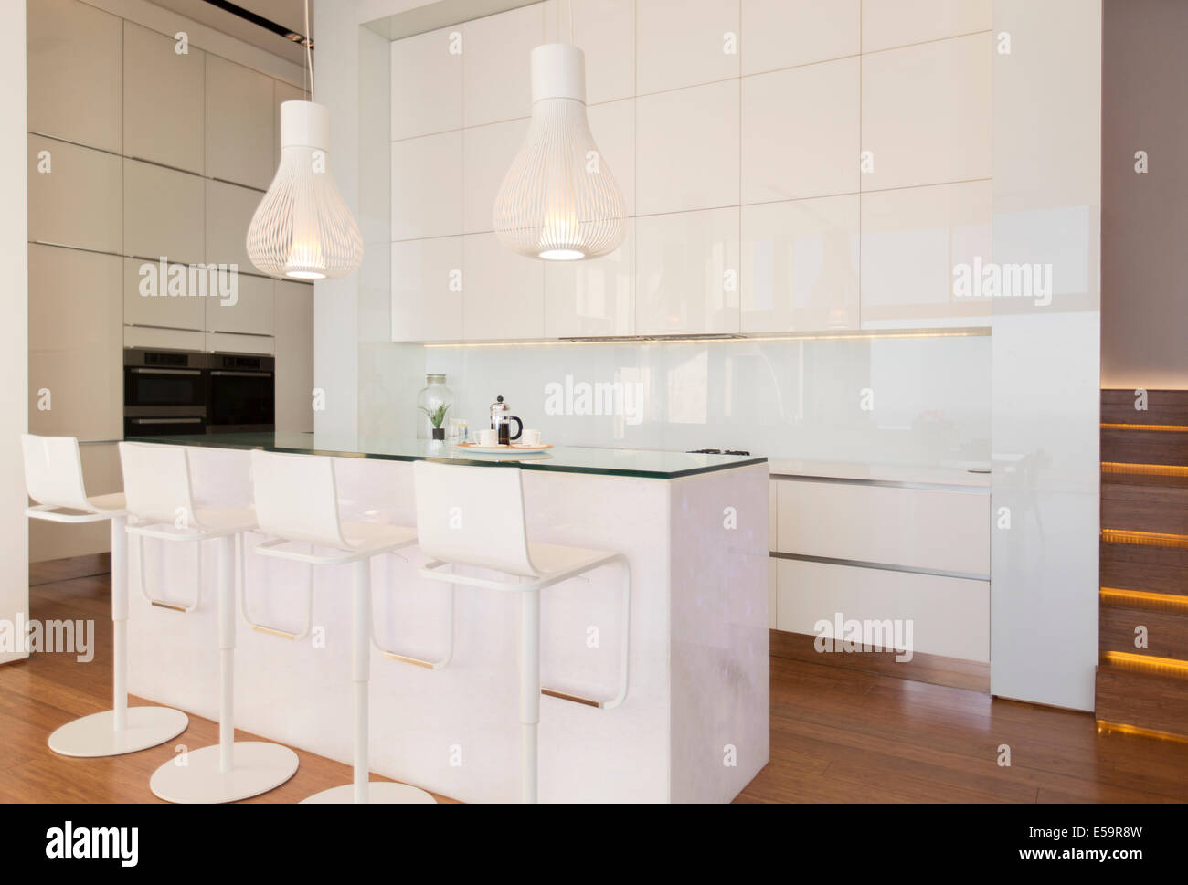Bar stools at counter in modern kitchen - Stock Image
