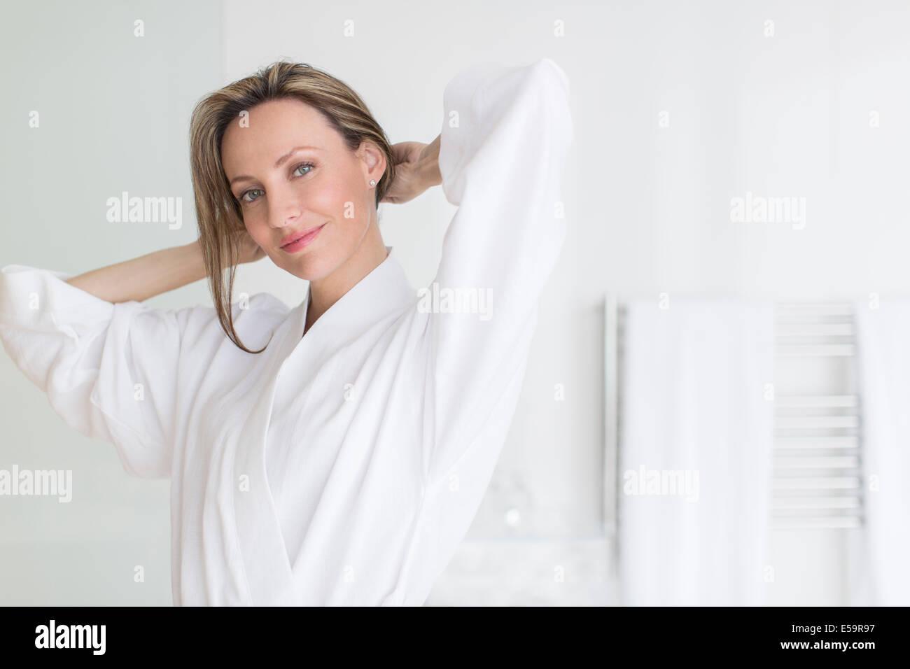 Smiling woman wearing bathrobe - Stock Image