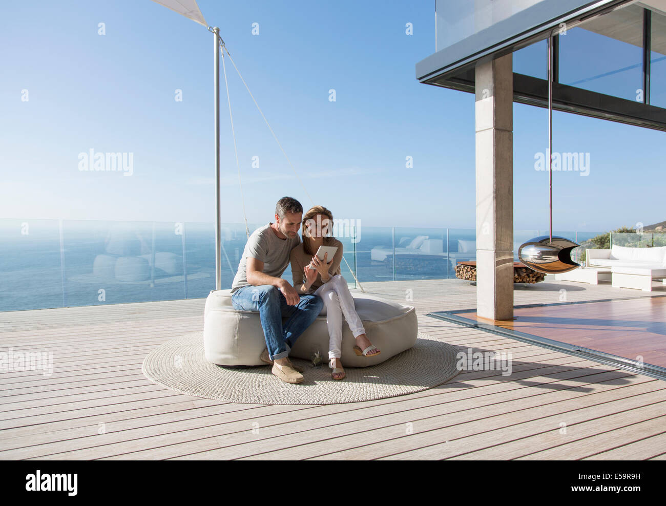 Couple using digital tablet on modern balcony - Stock Image