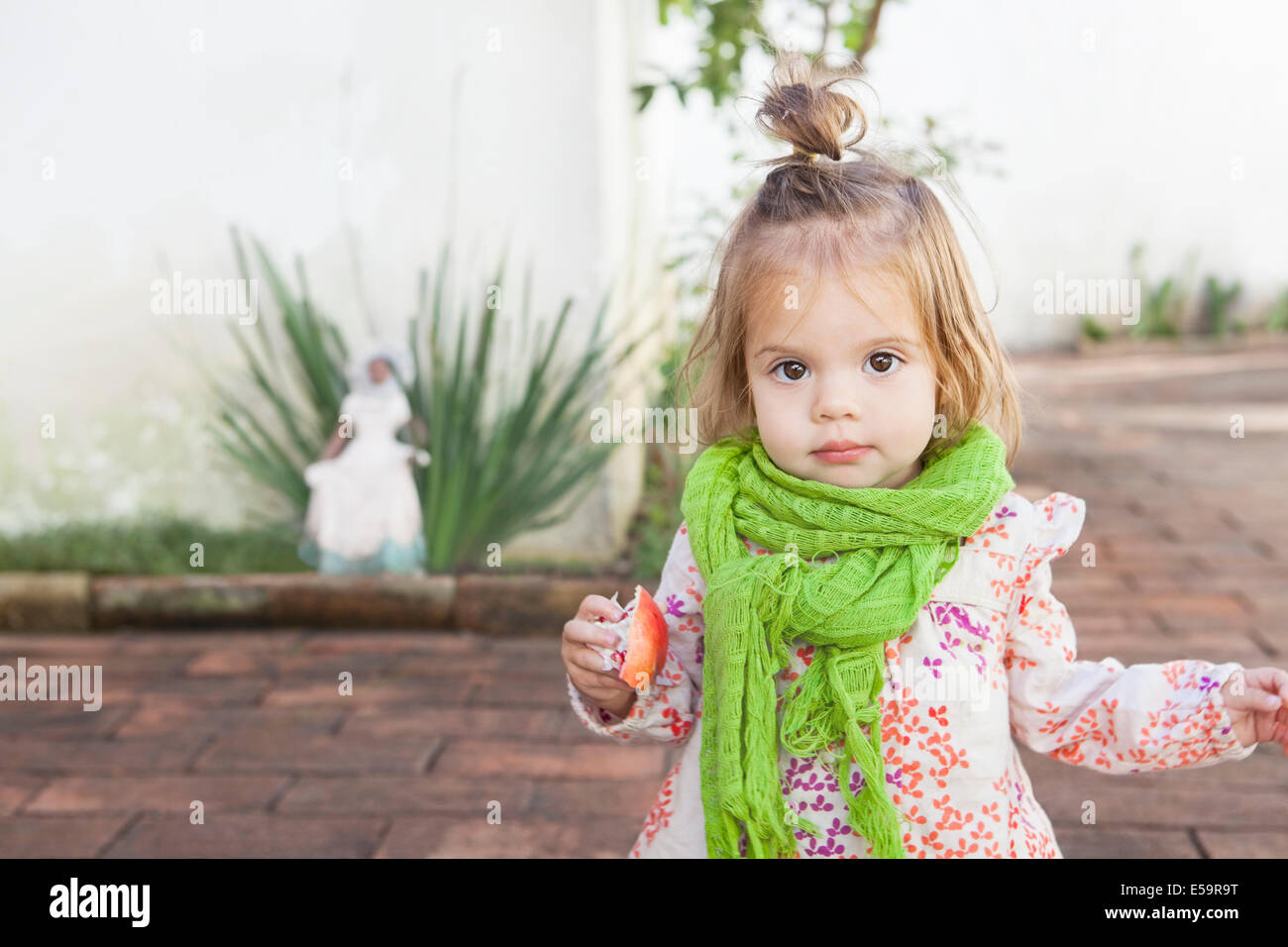 Baby girl eating fruit outdoors - Stock Image