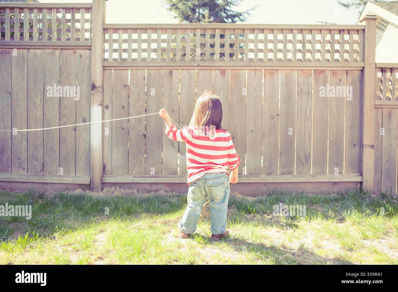 Baby girl playing with string in backyard - Stock Image