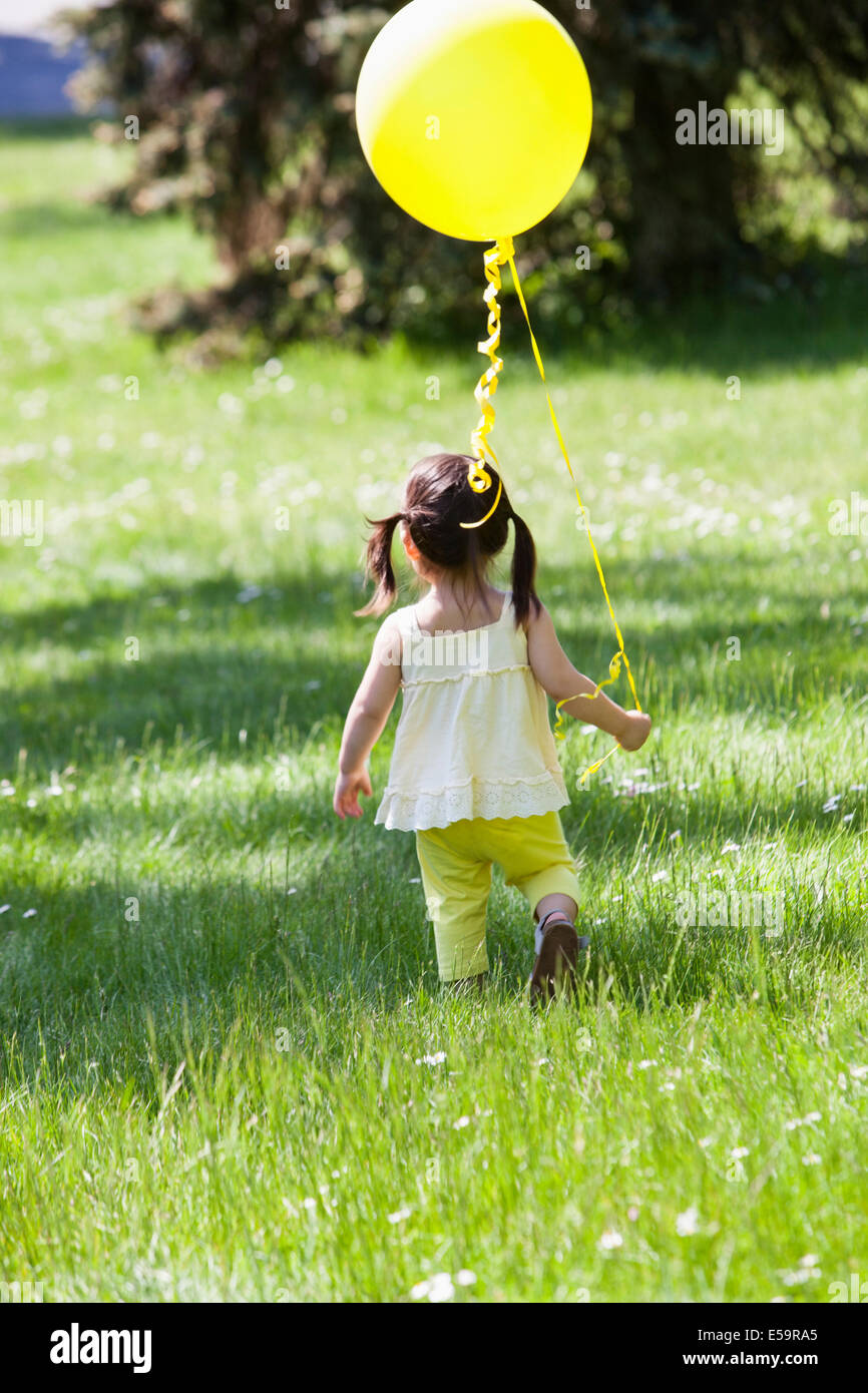 Girl carrying balloon in backyard - Stock Image