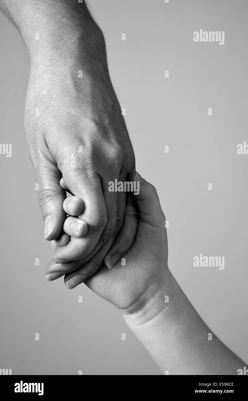 Adult or parent holding the hand of a small child - Stock Image