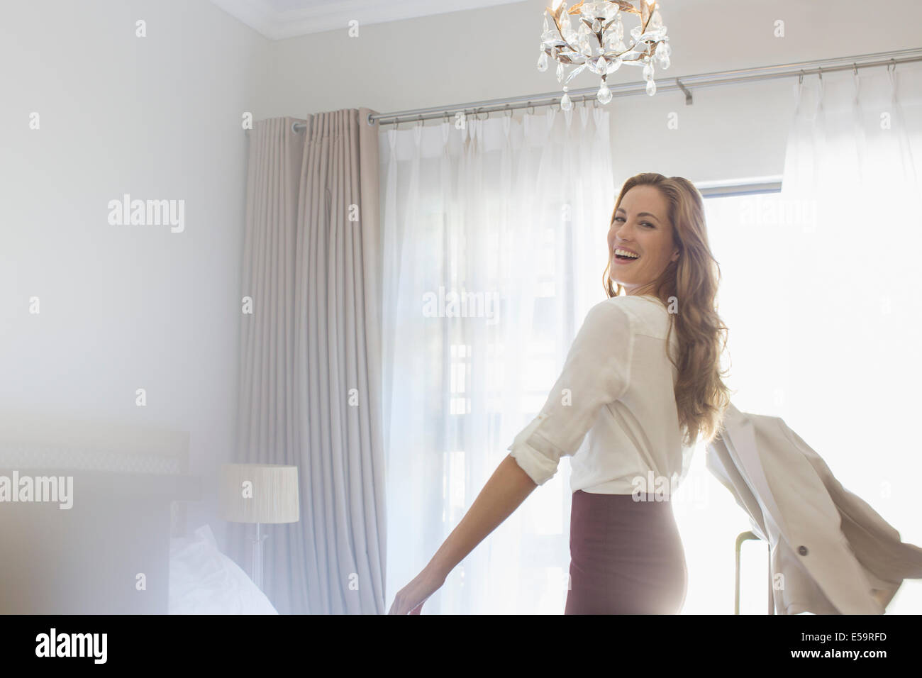 Businesswoman getting dressed in hotel room - Stock Image