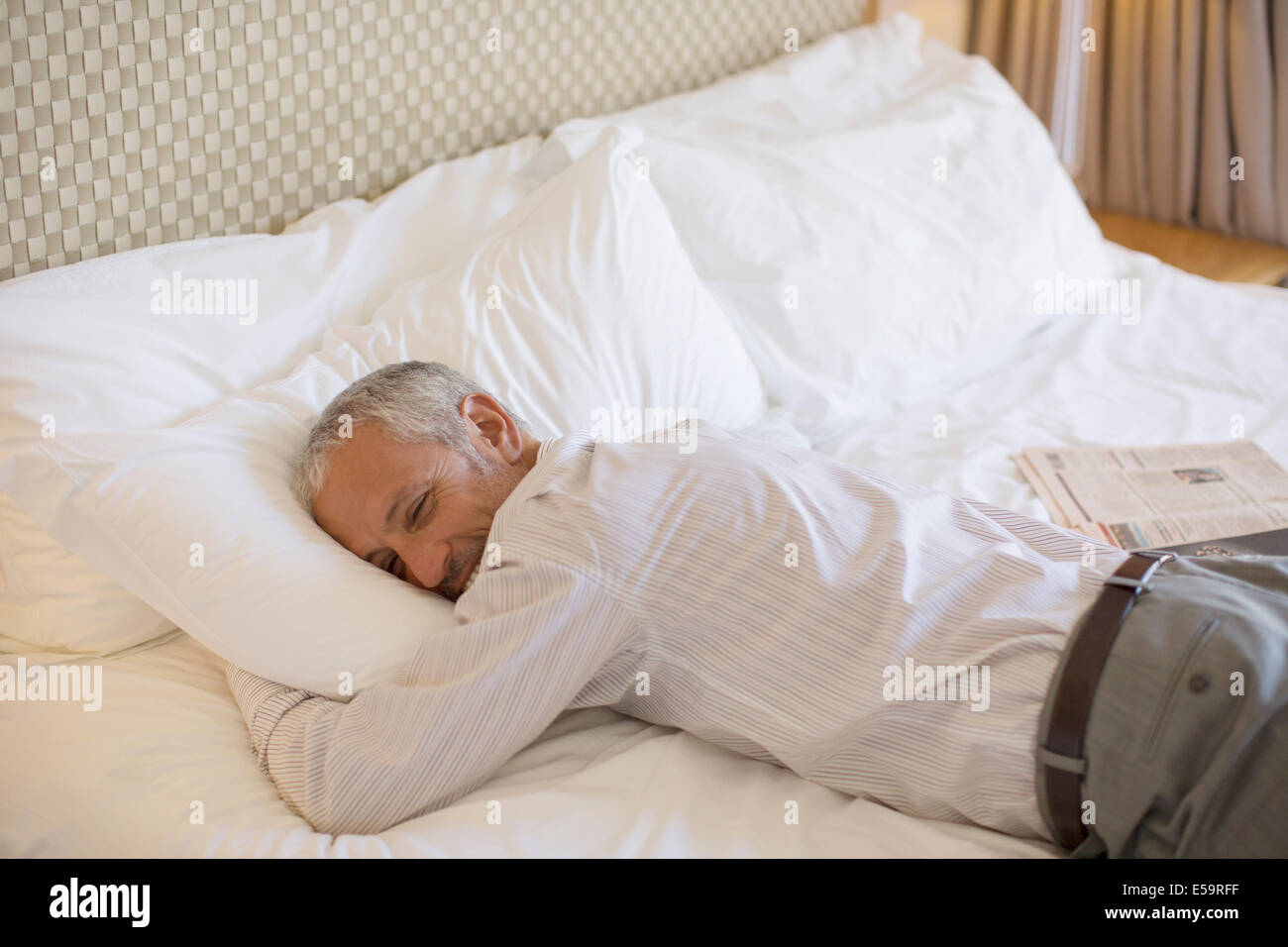 Businessman laying on bed in hotel room - Stock Image