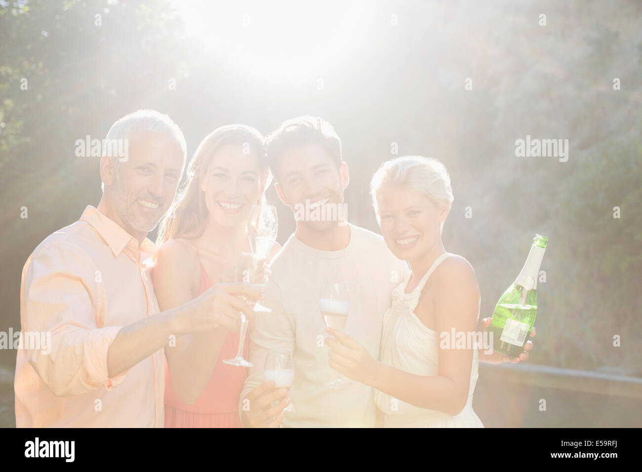 Friends toasting each other with champagne - Stock Image