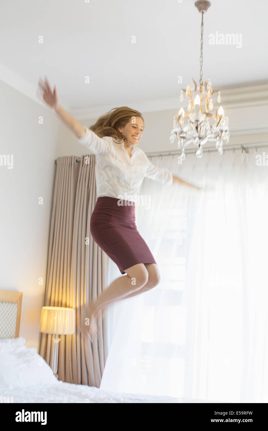 Businesswoman jumping on bed in hotel room - Stock Image