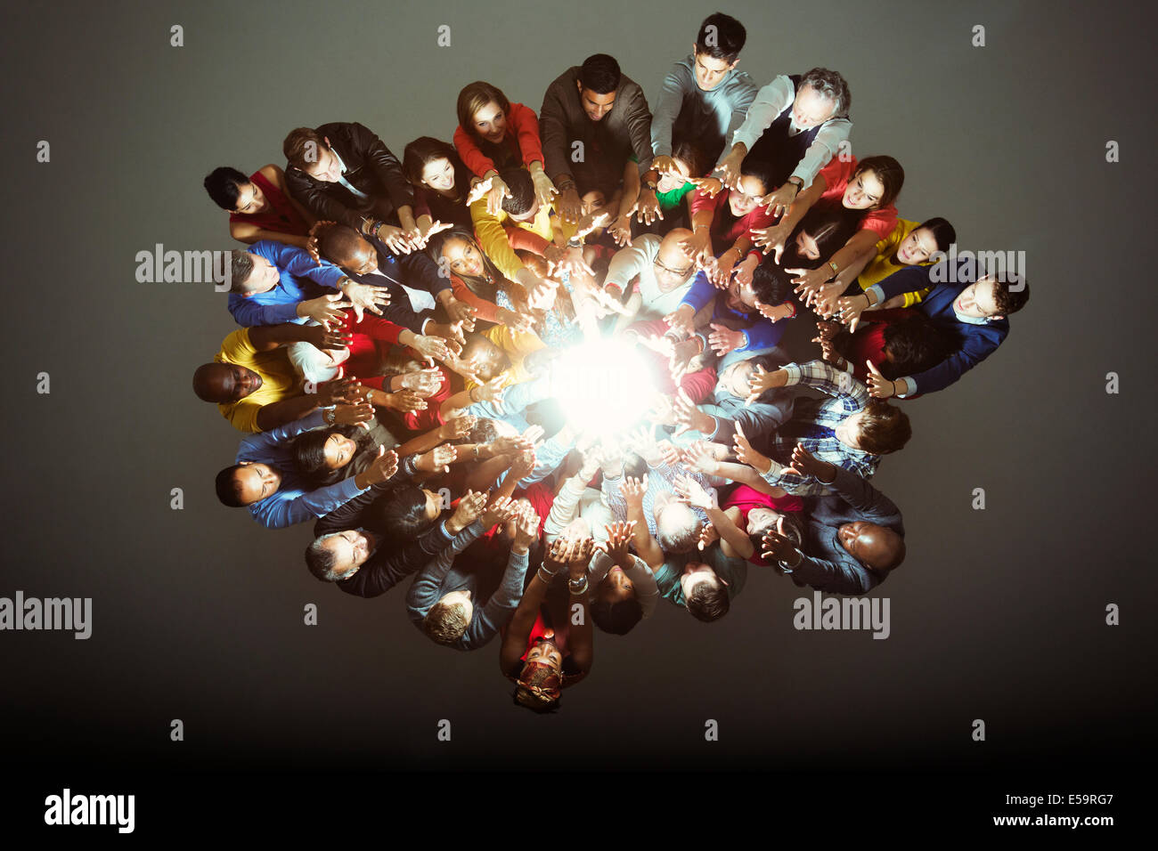 Diverse workers around bright light Stock Photo