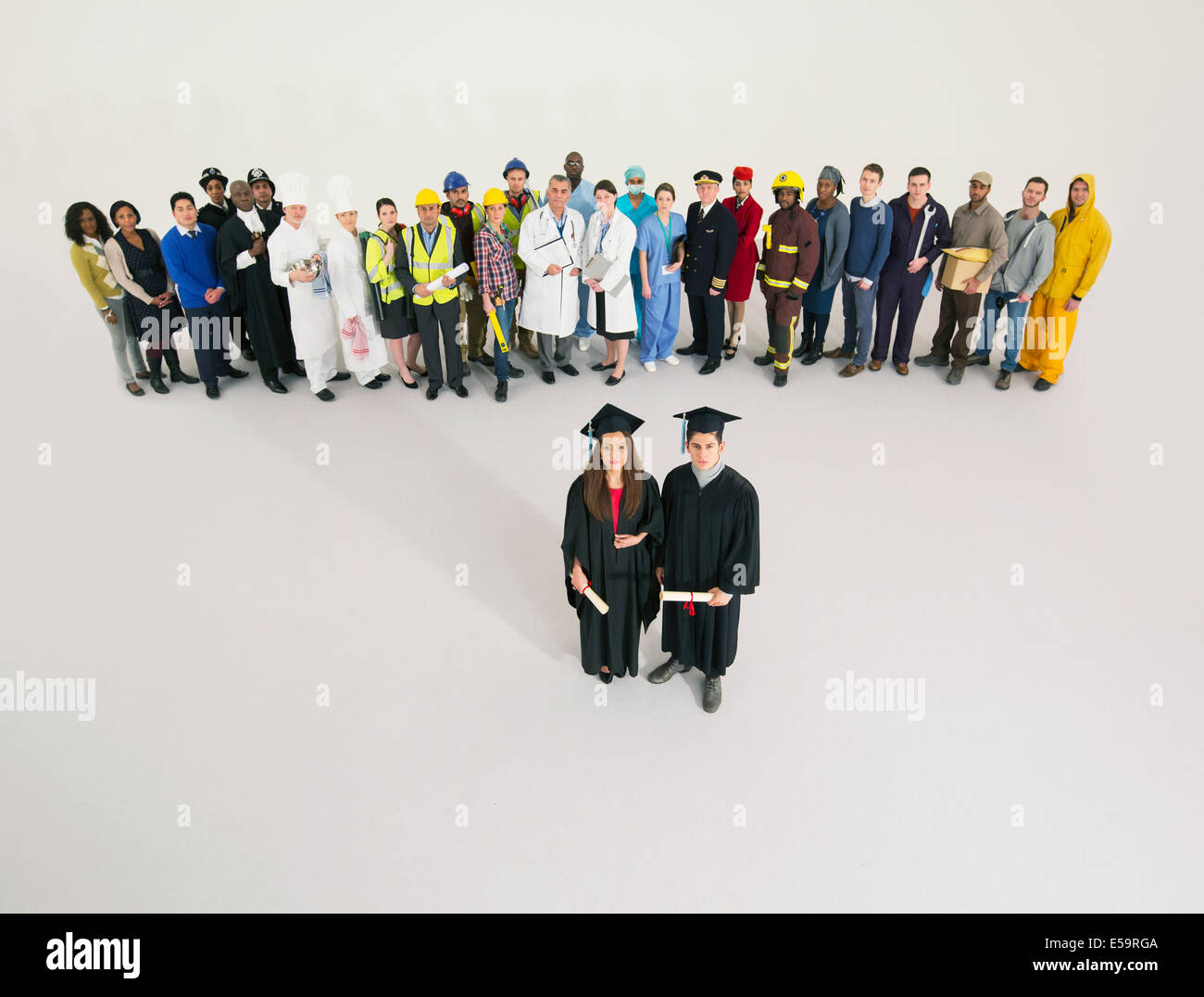 Portrait of graduates with workers in background - Stock Image