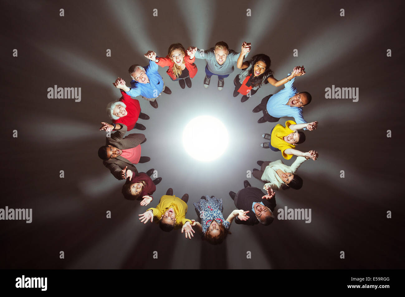 Diverse crowd around bright light - Stock Image