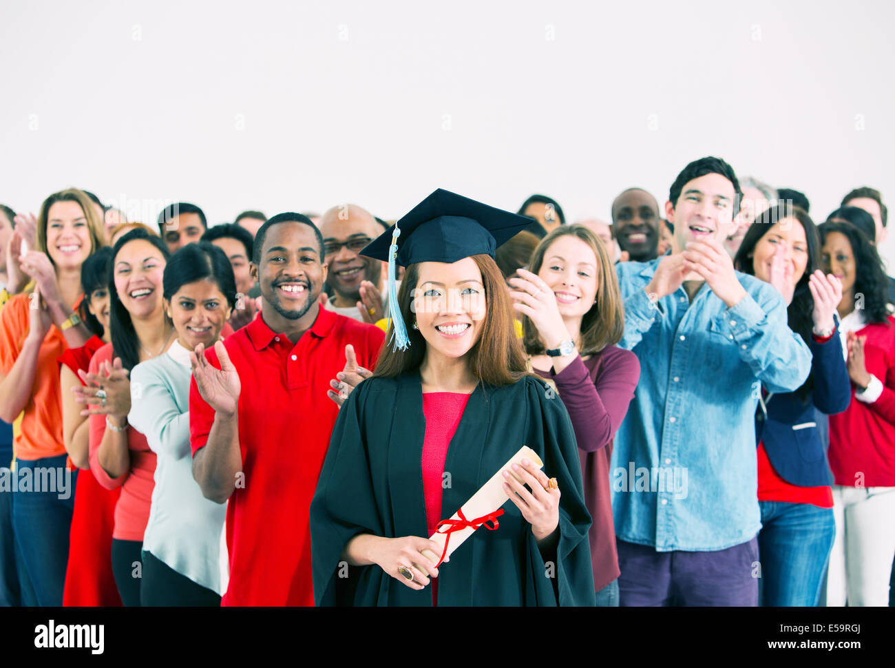 Crowd clapping behind happy graduate - Stock Image