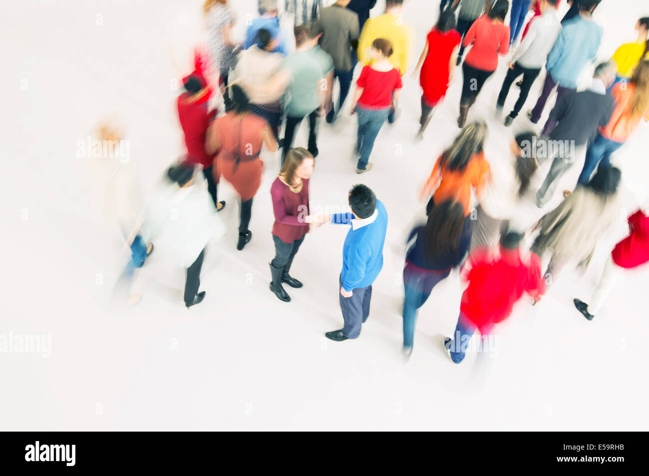 Business people handshaking in crowd - Stock Image