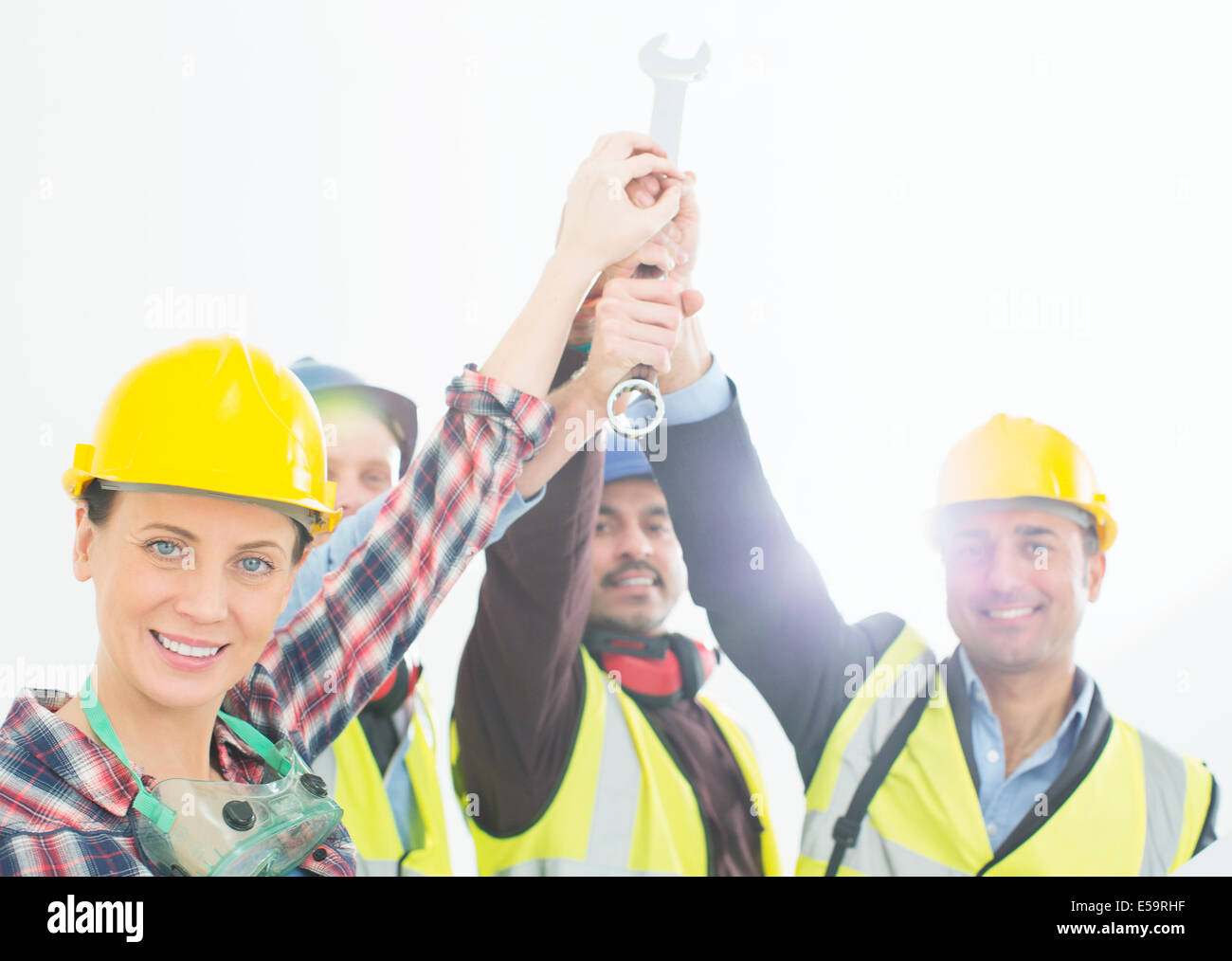 Portrait of construction workers joining hands - Stock Image