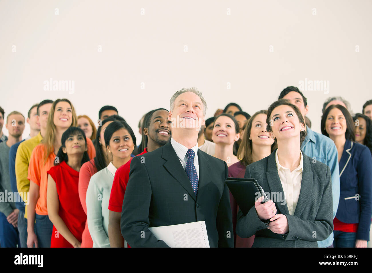 Crowd of business people looking up - Stock Image