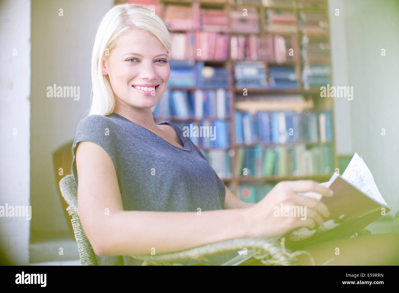 Woman reading in armchair - Stock Image