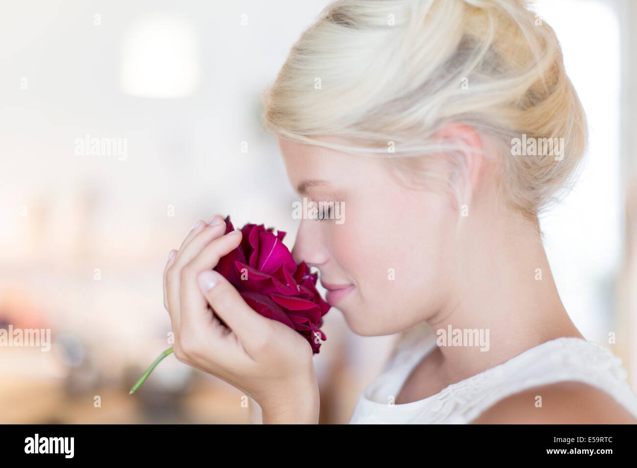 Woman smelling rose - Stock Image