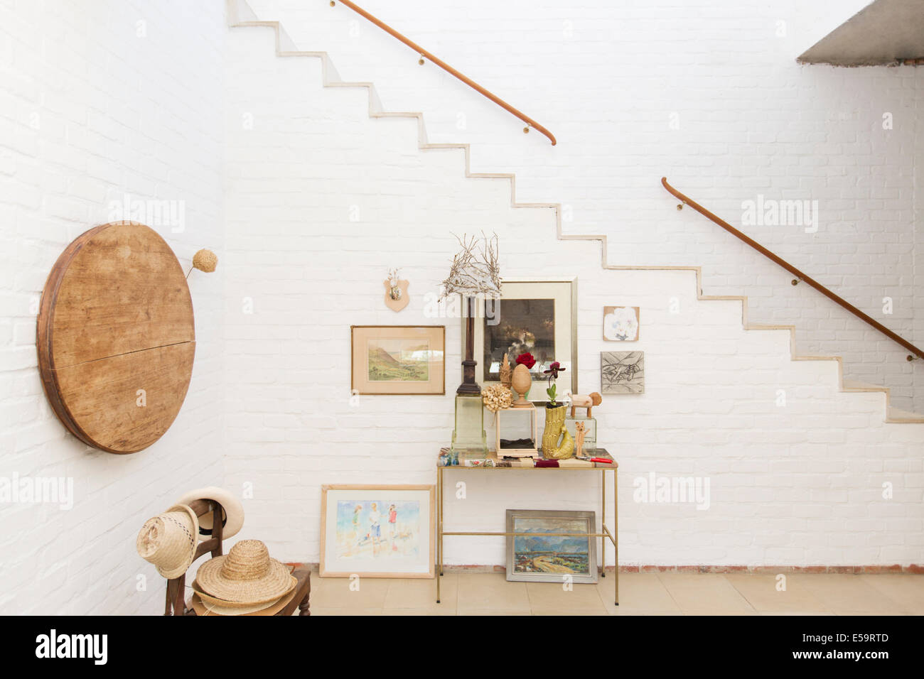 Side table and wall hangings by staircase - Stock Image