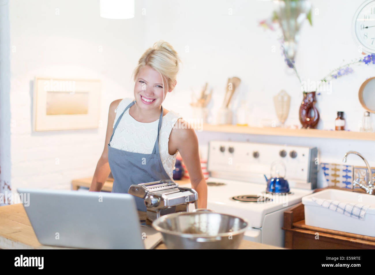 Woman at laptop cooking in kitchen - Stock Image
