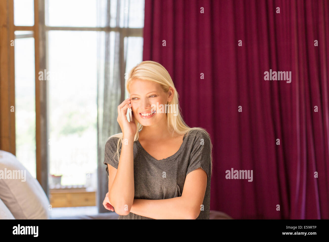 Woman talking on cell phone in bedroom - Stock Image