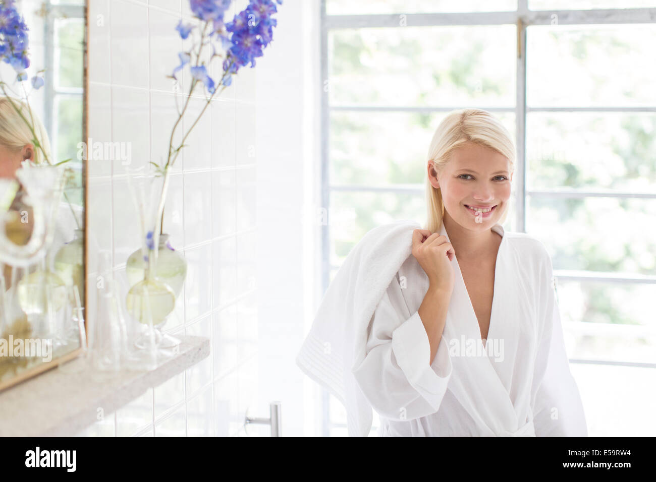 Woman in bathrobe smiling in bathroom - Stock Image
