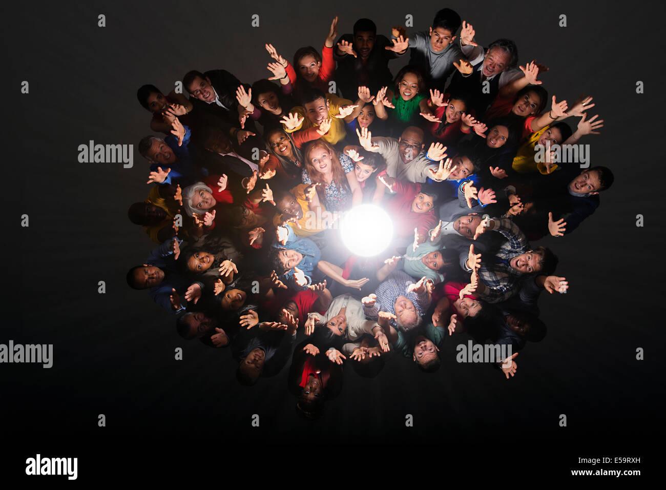 Diverse crowd cheering around bright light - Stock Image