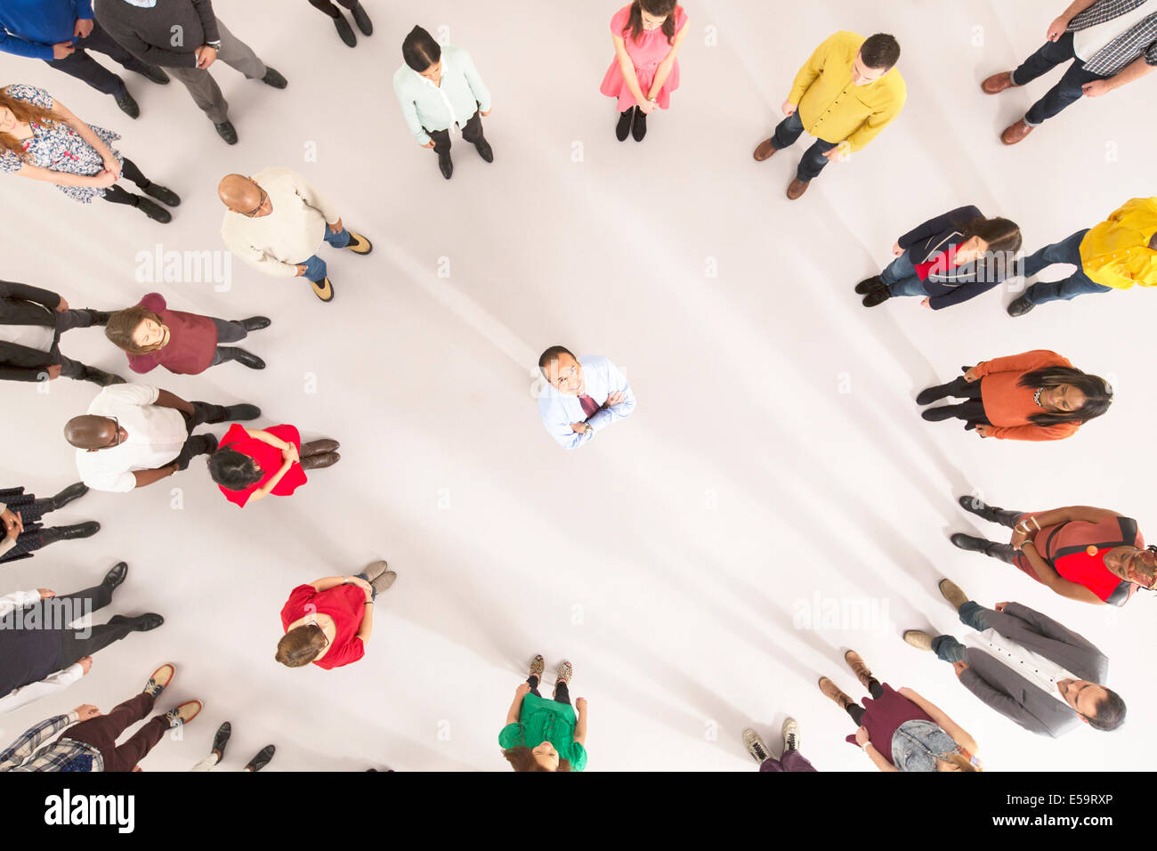 Crowd around businessman with arms crossed - Stock Image