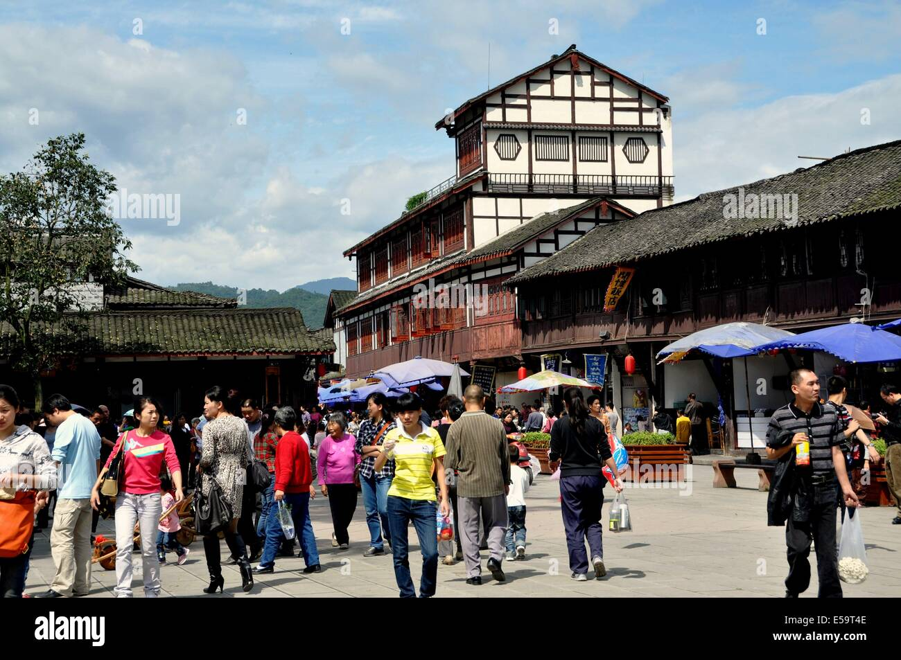 JIEZI ANCIENT TOWN, CHINA: A unique wooden and stuccoed house towers over the Wastepaper Library Square thronged - Stock Image