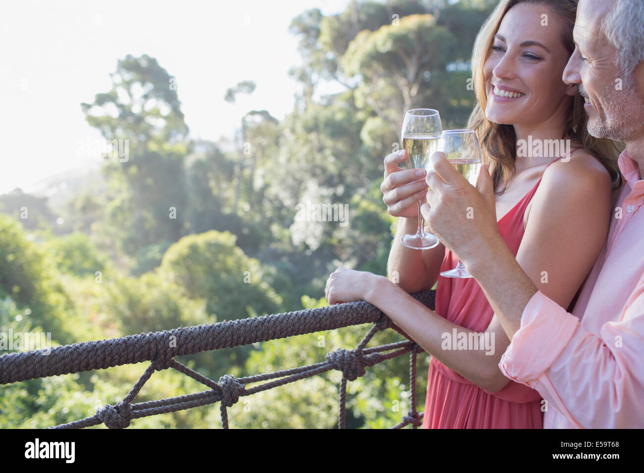 Couple toasting each other on balcony - Stock Image