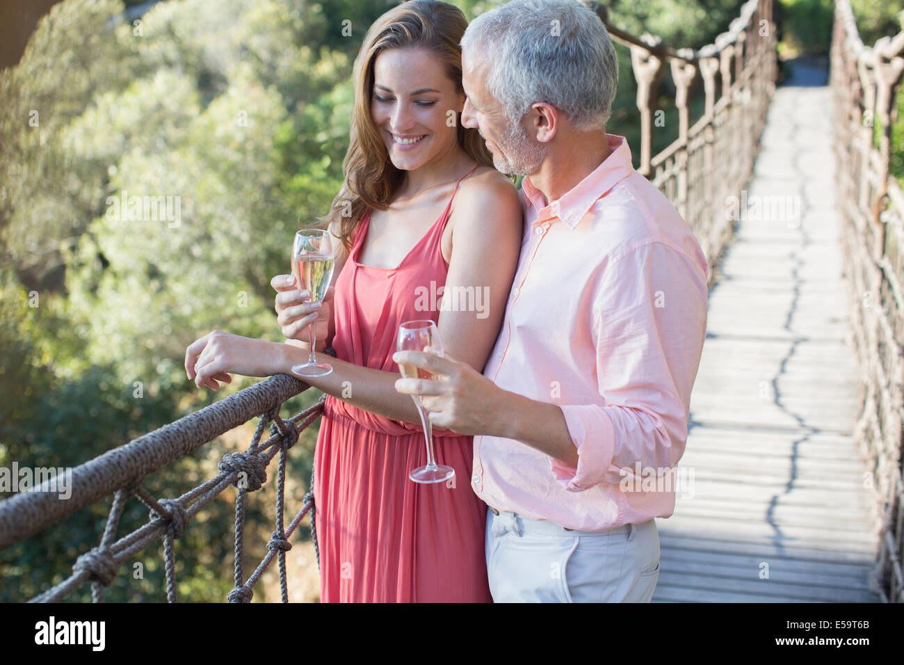 Couple toasting each other on wooden rope bridge - Stock Image