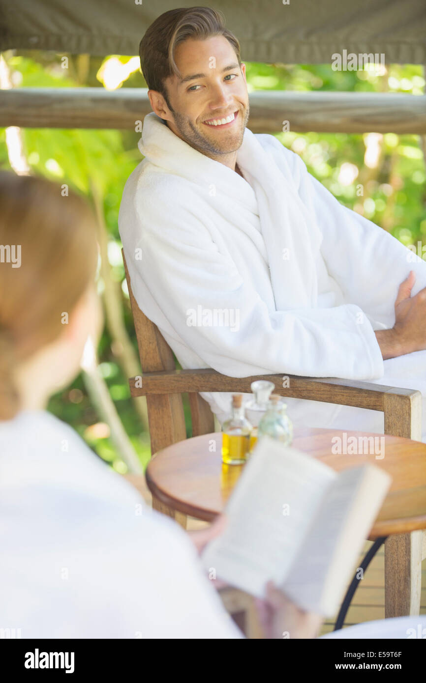 Couple relaxing together in bathrobes - Stock Image