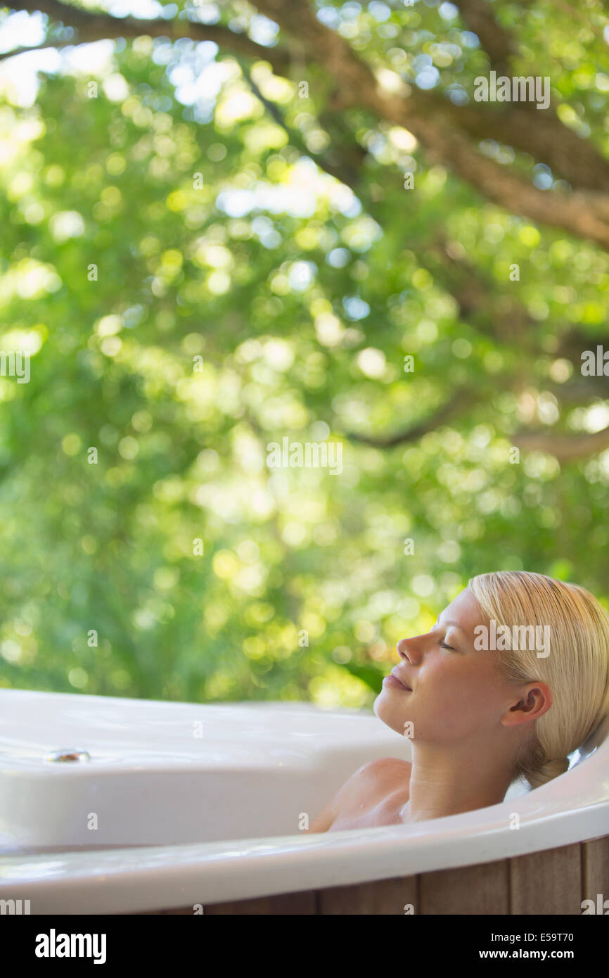 Woman relaxing in hot tub - Stock Image