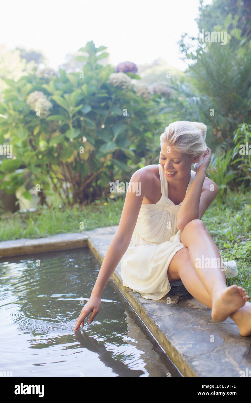 Woman sitting by pool - Stock Image