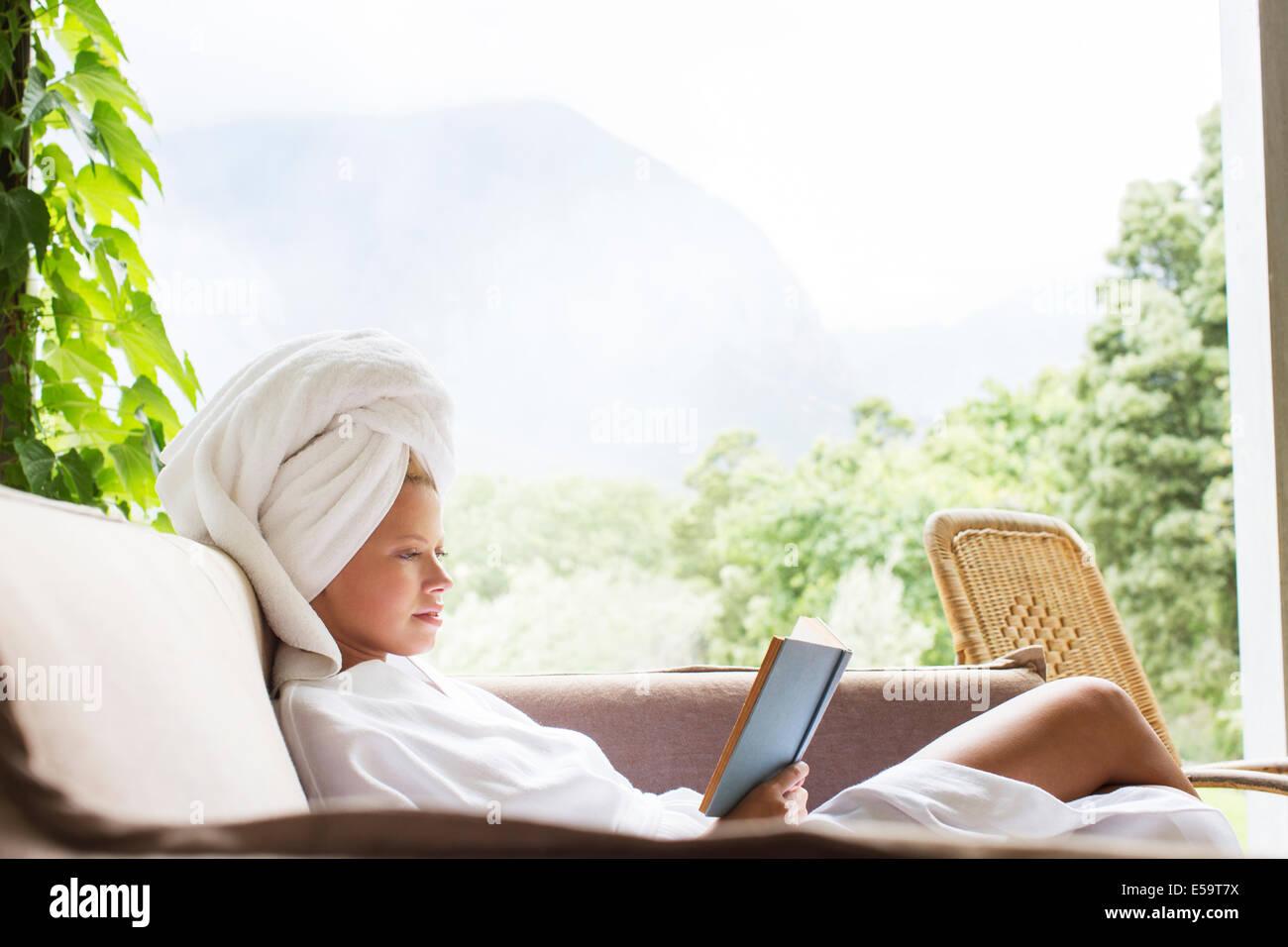 Woman in bathrobe reading on sofa - Stock Image
