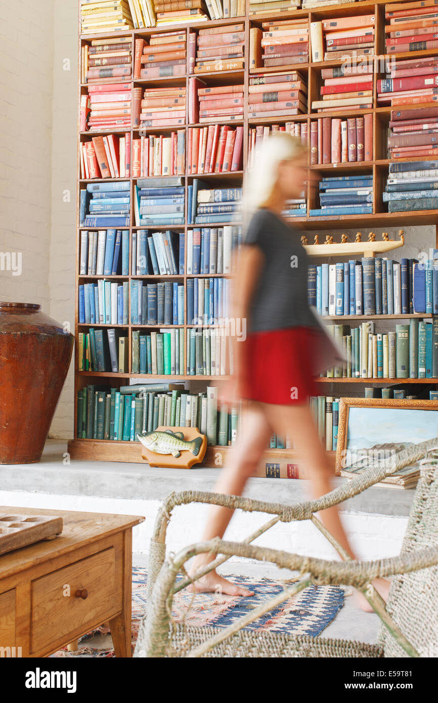 Blurred view of woman walking by bookcase - Stock Image