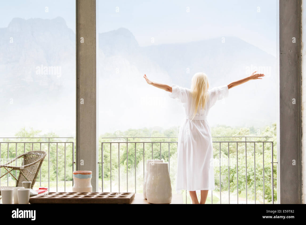 Woman in bathrobe overlooking landscape - Stock Image