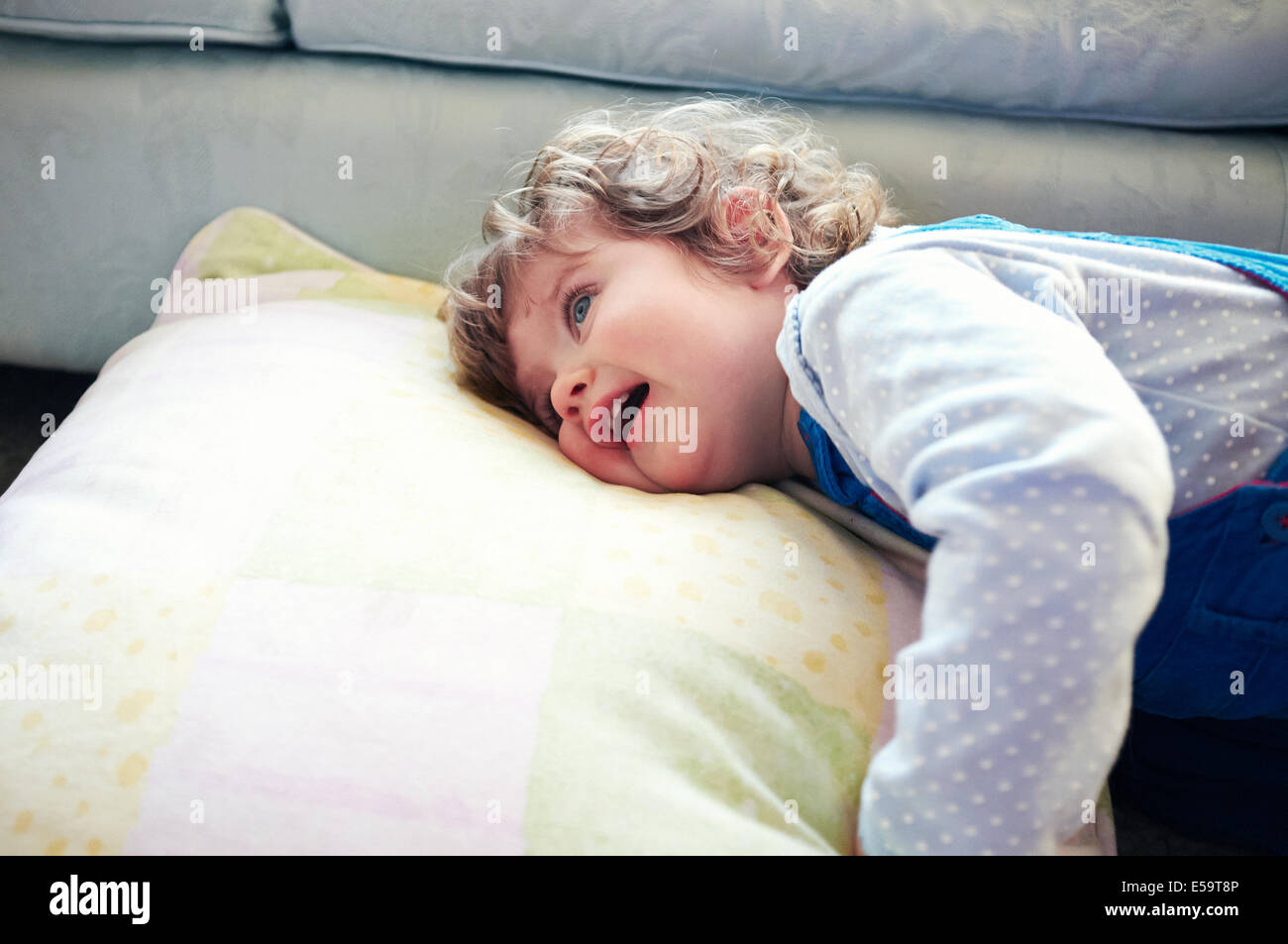 Girl laying on pillow in living room - Stock Image